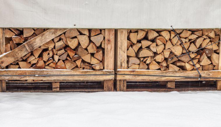 Zwei Stapel abgedecktes Feuerholz im Winter, auf Paletten gelagert
